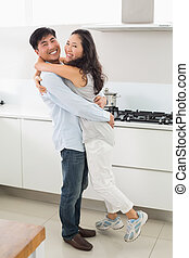 Side view portrait of a young couple in kitchen