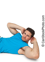 Side view portrait of a young man doing abdominal crunches