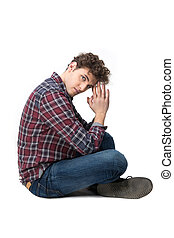 Side view portrait of a young man sitting on the floor