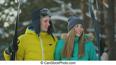 Side view portrait of active young couple enjoying skiing in beautiful winter forest, focus on unrecognizable woman holding ski poles, copy space
