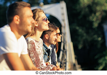 Side view portrait of four young friends standing on bridge...