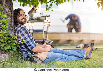 Side view portrait of happy carpenter holding mobilephone and disposable cup while leaning on tree trunk