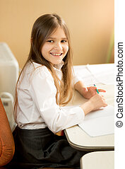 Side view portrait of smiling schoolgirl writing at exercise book