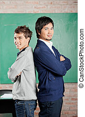 Side view portrait of young male students standing hands folded against greenboard in classroom