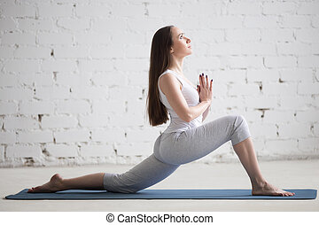 Side view portrait of young woman doing yoga in white loft
