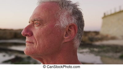 Side view senior man at beach - Side view close up of a ...