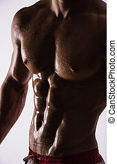 Side-view silhouette of young muscular athletic sexy shirtless hot man posing showing wet sport body with cool pectoral abs muscle strong breast biceps studio on white. Beads sweat training gym.