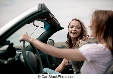 side view. two girlfriends enjoying a ride in the car