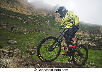 Side view wide angle partly a man on a mountain bike travels on rocky terrain Against the background of cloudy sky and epic rocks. The concept of a mountain bike and mtb downhill
