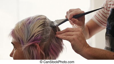 Alternative cool hair salon. Side view close up of a Caucasian male hairdresser working in a hair salon, holding brush, colouring hair of a Caucasian female client in slow motion
