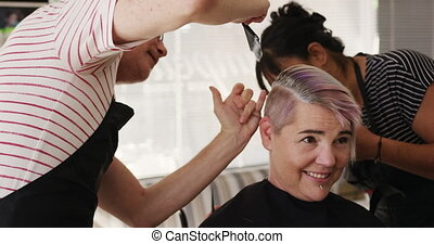 Alternative cool hair salon. Front view of a happy Caucasian male hairdresser working in a hair salon, holding brush, colouring hair and discussing with a Caucasian female client in slow motion
