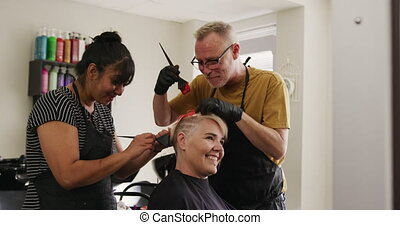 Alternative cool hair salon. Side view of a Caucasian male and mixed race female hairdressers working in a hair salon, holding brushes, colouring hair of a Caucasian female client in slow motion