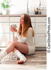 Side view woman holding cup, sitting on a floor