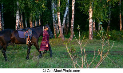 side view woman leads horse under bridle by birches