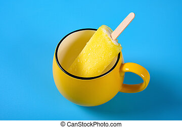 side view yellow popsicle in a cup on blue background