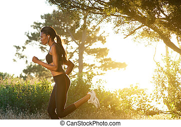 Side view young black woman running in nature