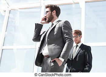 side view.business man talking on mobile phone