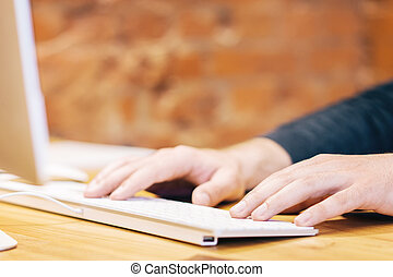 Sideview of businessman hands using keyboard