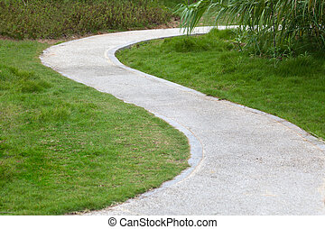Lawn, reed, small tree, and curved sidewalk around grass.