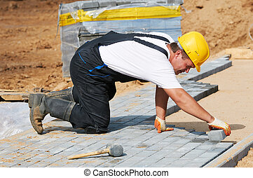 sidewalk pavement construction works - mason worker making ...