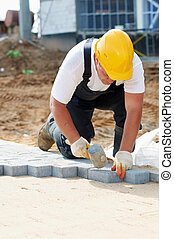 sidewalk pavement construction works - mason worker making ...