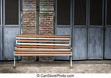Sidewalk scene with wooden bench and brick wall.