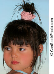 Face of a little girl with a top knot hair style.