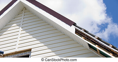 Siding against the sky - Installation of a siding on a house...