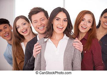 sie, gleichfalls, echte , leader., attraktive, junge frau, lächeln, während, gruppe, von, heiter, junge leute, stehen, sie, in, zwei, reihen