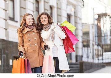sie, weiß, wohin, ar, der, am besten, prices., zwei, schöne , junge frauen, stehende , mit, einkaufstüten, in, ihr, hände, während, eins, von, sie, zeigen, weg
