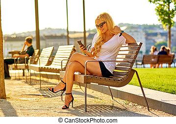 siedząc, kobieta, jej, młody, ława, telefon, używając