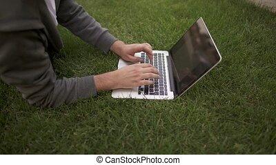 sien, ordinateur portable, jeune, unrecognizable, homme, dactylographie, pelouse, côté, mensonge, vue