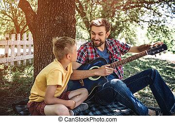 sien, séance, très, ajustement, guitar., père, fils, regarder, excited., dad., enfant avoirs, fin, couverture, il