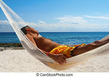 Siesta - Goodlooking man, asleep in a hammock on a tropical...