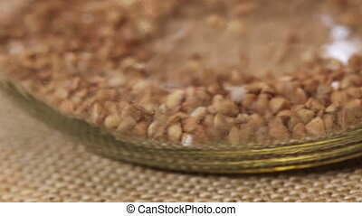 Sifting buckwheat in glass jar
