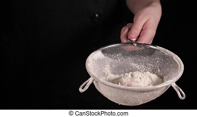Baker sifting white wheat flour through a sieve on black background in slow motion
