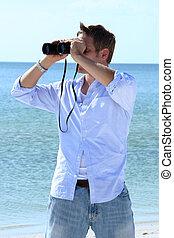 Man on beach looking through binoculars