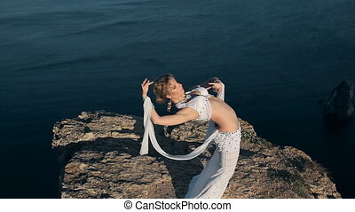 Sightly girl shows all the beauty of oriental dance standing on a mountain in Crimea