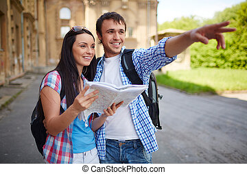 Sightseeing - Couple of travelers with map sightseeing in...