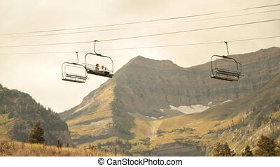 sightseers on chairlift with mountain in distance