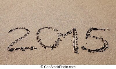 Sign 2015 drawn in the sand, water rushes over and washes it away