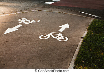 sign cyclist and the direction arrow on the background of asphalt road.