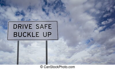 Road sign that says DRIVE SAFE BUCKLE UP with a time-lapse clouds background.