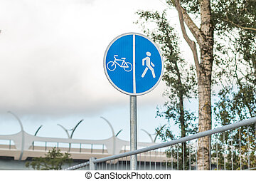 Sign for pedestrians and cyclists near a road in the park. Close up shot. Bicycle and Walking Path Sign with Sky Background. Copy space. Sport outside. Bicycle and pedestrian blue sign, board