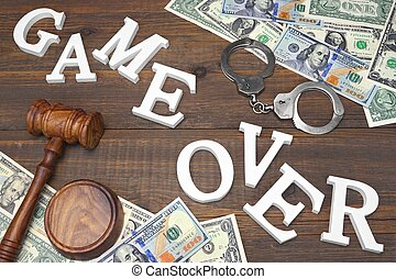 Sign Game Over, Money, Handcuffs, Judges Gavel On Wood Background