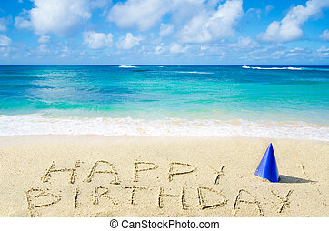 "Sign ""Happy Birthday"" with hat on the sandy beach by the ocean"
