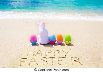 """Sign """"Happy Easter"""" with bunny and color eggs on the beach"""
