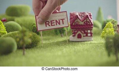 Sign house For Rent in an area with green grass, trees and hills.