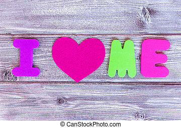 Sign i love me made of colorful letters and a heart on wooden background, self loving concept