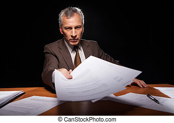 Sign it! Serious senior man in formalwear sitting at his working place and stretching out documents while isolated on black background